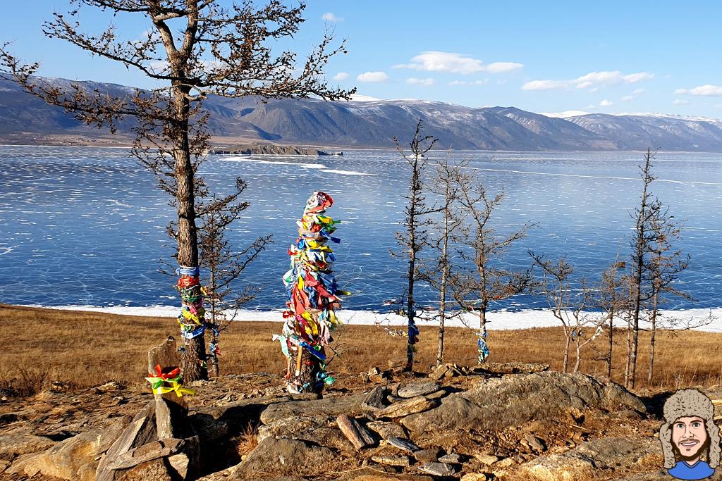 Blick auf den gefrorenen Baikalsee mit Bäumen und bunten Bändern