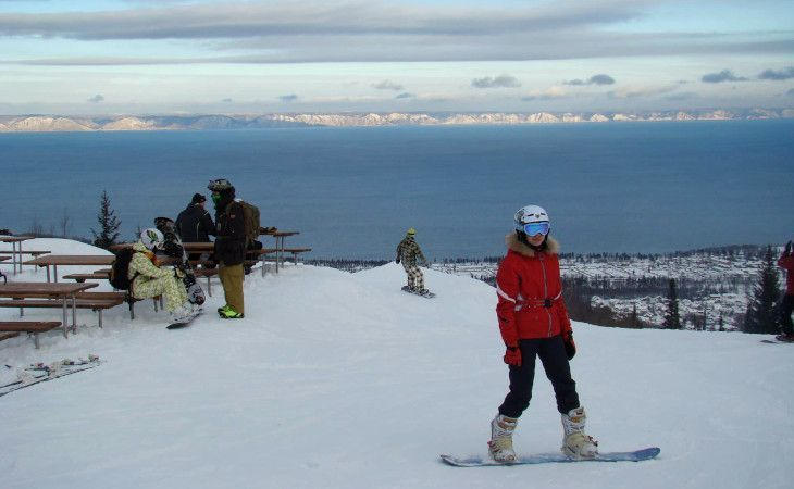 Snowboarderin auf dem Zobelberg mit dem Baikalsee im Hintergrund