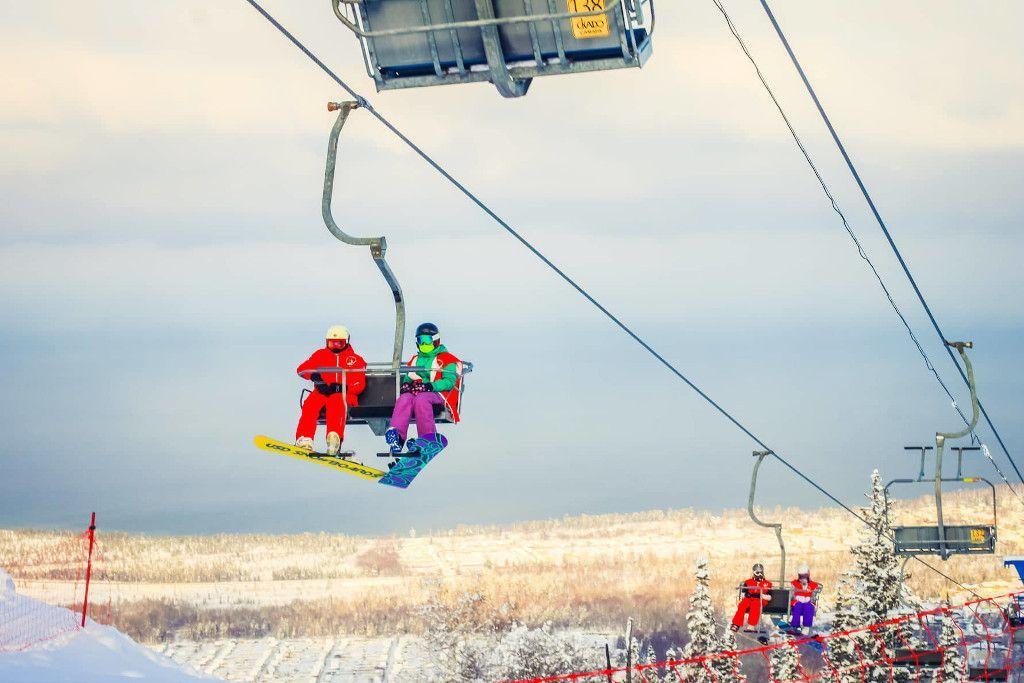 Sessellift mit Snowboad fahrenden Menschen in Baikalsk