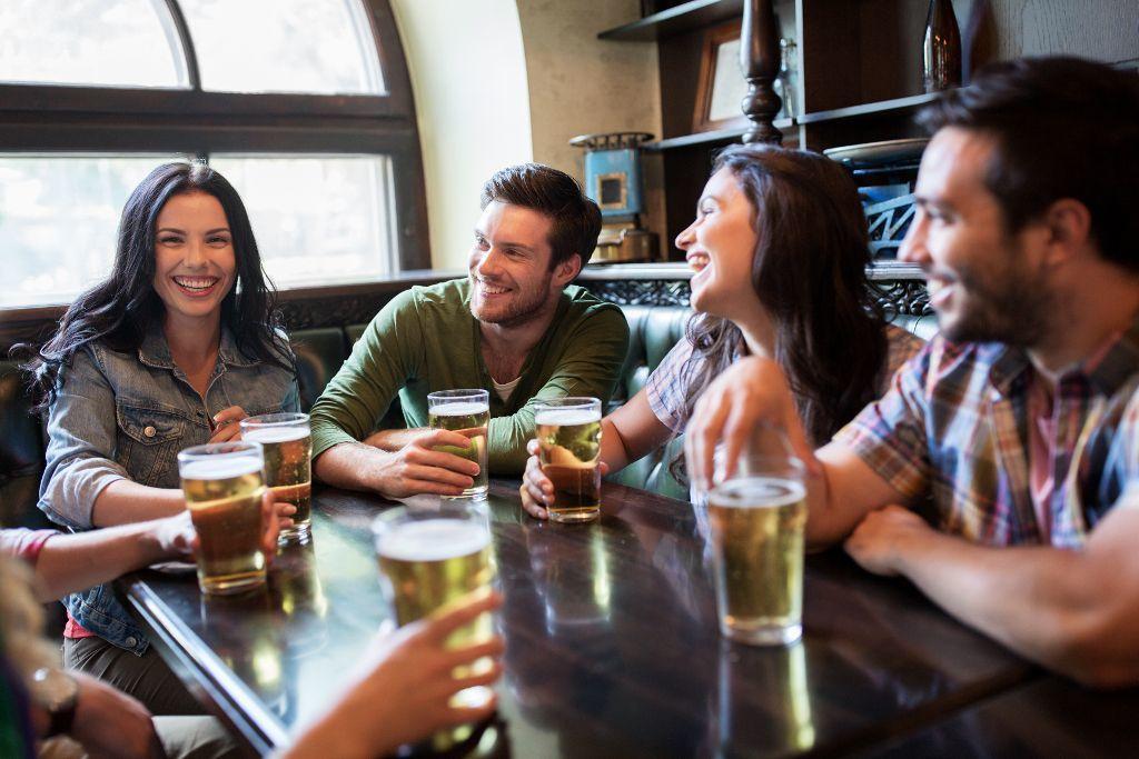 Lachende Menschen in einer Bar mit Bier