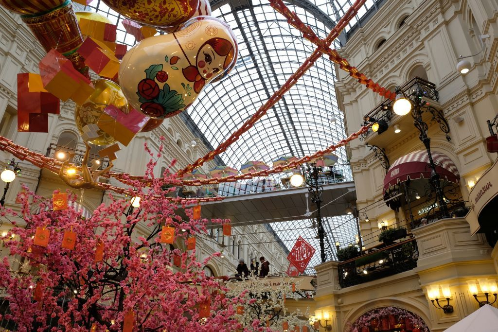 Deckendekoration und rosaroter Blütenbaum im GUM Kaufhaus in Moskau