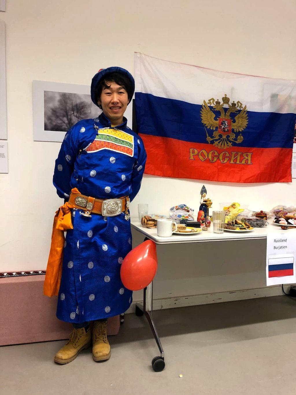 Mann in burjatischer Nationalkleidung neben einer russischen Flagge