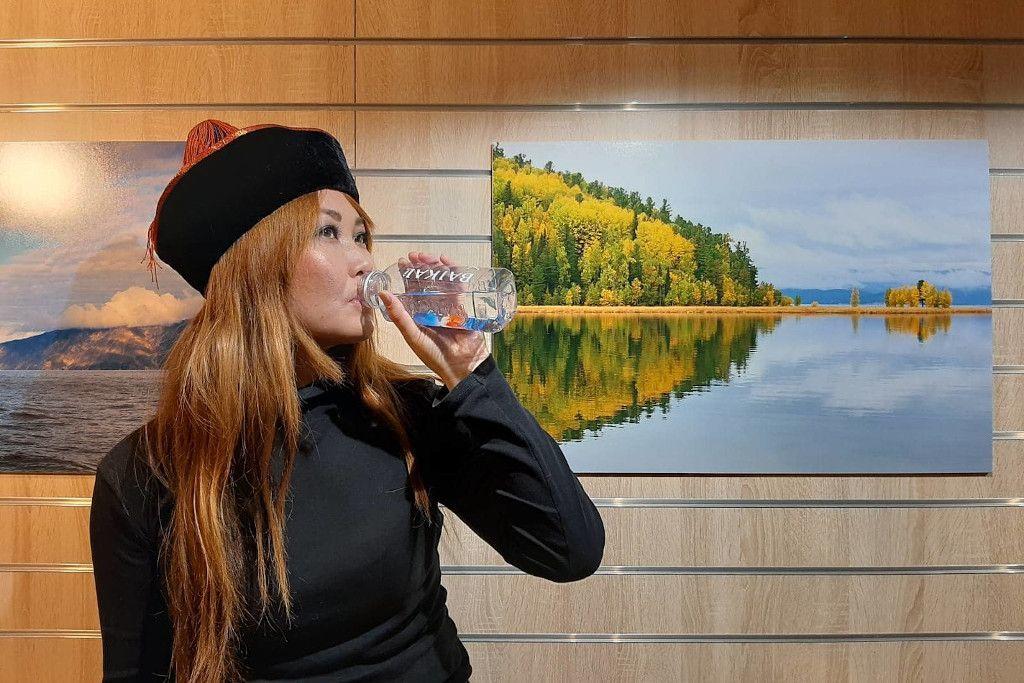 Burjatin trinkt Wasser vor Bildern einer Ausstellung
